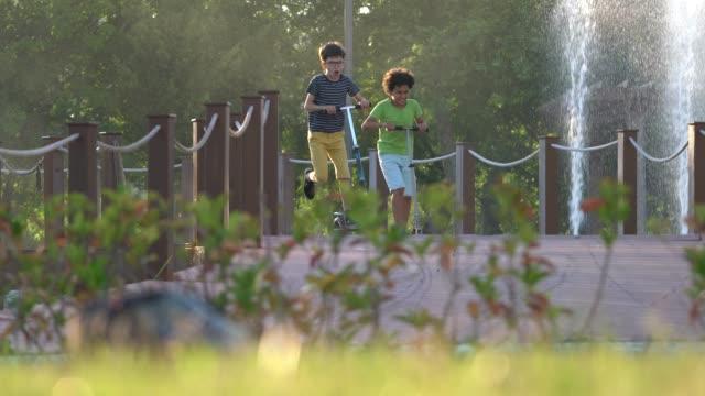 stockvideo's en b-roll-footage met gelukkige jongens met scooter in een park - schooljongen