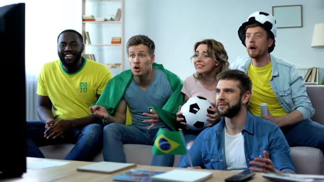Amigos brasileiros felizes assistindo partida de casa comemorando gol do time de futebol - vídeo