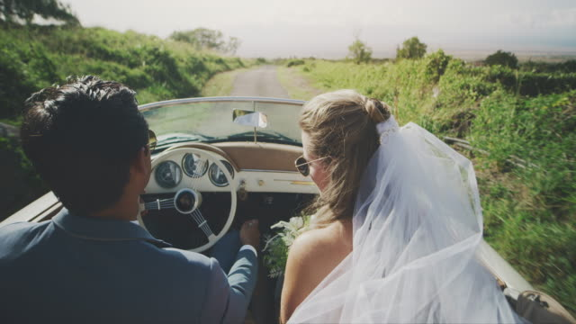 Happy bride and groom driving together in the countryside