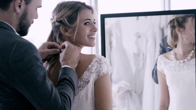 stockvideo's en b-roll-footage met gelukkige bruid en bruidegom in trouwjurk bereiden voor getrouwd in huwelijksceremonie. - halsketting