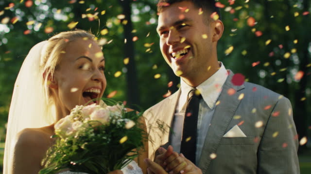 happy bride and groom laugh and are surprised by confetti in a sunny park. - помолвка стоковые видео и кадры b-roll