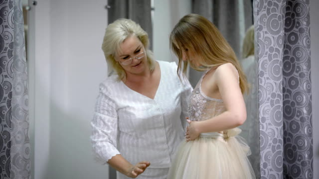 Happy bride is standing and fitting dress in atelier with wedding assistant. Young woman with dressmaker are making final touch on tailor made gown in custom clothing shop video