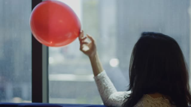 Happy Bride sitting with balloon and rose petals in front of view video