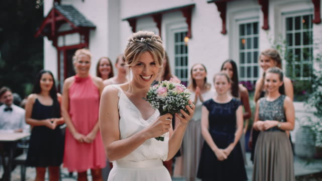 happy bride throwing bouquet to wedding guests - pojęcia i zagadnienia filmów i materiałów b-roll