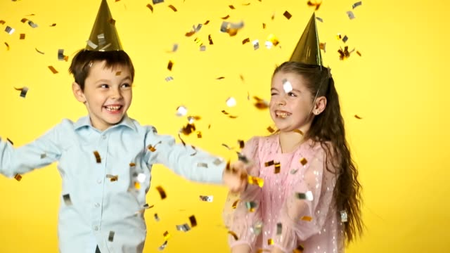 Happy brother and sister throwing confetti. Excited laughing kids in party caps Happy brother and sister throwing golden confetti. Excited laughing kids in party caps under sparkling confetti shower. Children birthday party. Slow motion birthday background stock videos & royalty-free footage