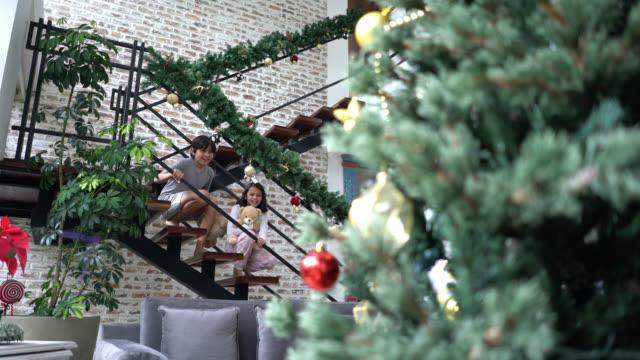 stockvideo's en b-roll-footage met gelukkig broer en zus lopen naar beneden de trap glelen in de kerstboom glimlachend - christmas tree