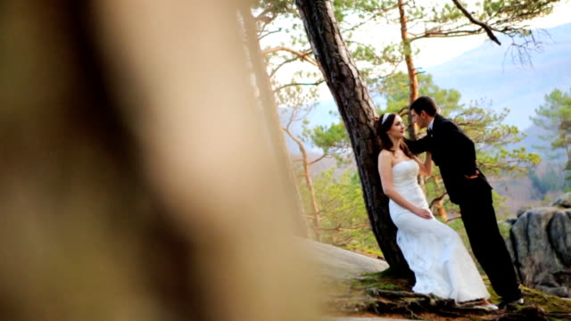 Happy brunette bride leaning against a tree looking at her handsome groom in pine forest