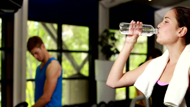 Happy brunette drinking water Happy brunette drinking water at gym arms akimbo stock videos & royalty-free footage