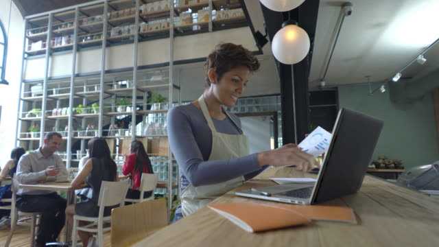 Happy business owner doing the books, while customers are at the back Happy business owner doing the books, while customers are at the back in the restaurant owner stock videos & royalty-free footage