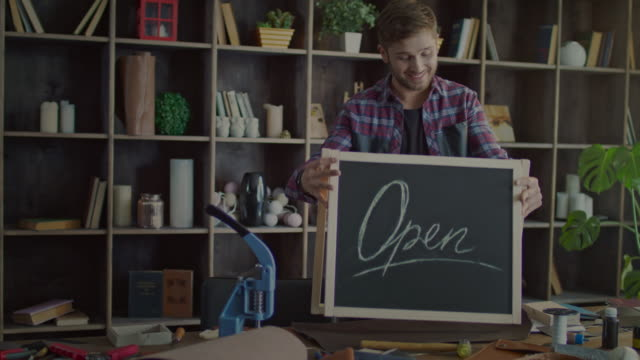happy business owner putting open sign on table in small shop - open sign stock videos & royalty-free footage