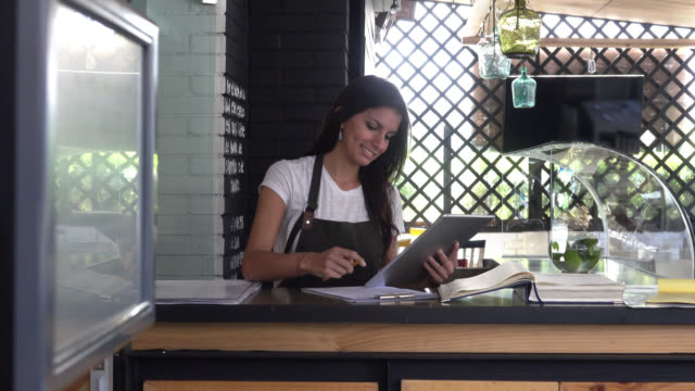 Happy business owner using a tablet computer doing the books video
