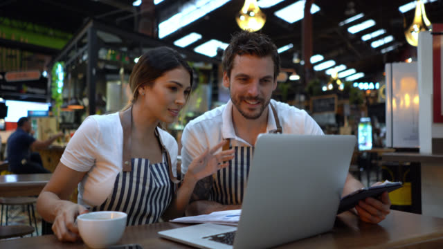 Happy business owners of a restaurant doing the books using a laptop and paperwork- video