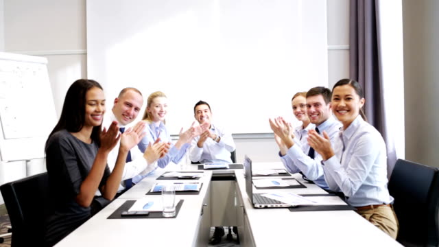happy business team applauding at office conference corporate, people and greeting concept - happy business team with laptop computer and papers applauding at office conference board room stock videos & royalty-free footage