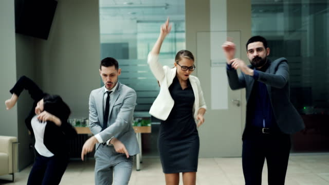 happy business team men and women are dancing at work party together moving bodies, laughing and singing relaxing in hall. coworkers, relaxation and emotions concept. - праздничное событие стоковые видео и кадры b-roll