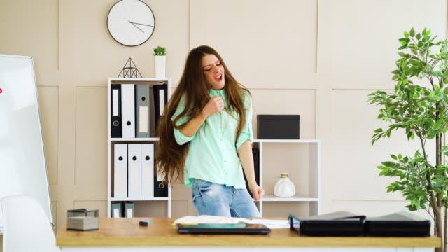 Happy business woman dancing in office at work break video