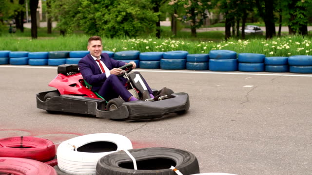 Happy businessman having fun on a racing track. Funny young businessman in a suit driving Go-Kart car in a playground racing track. go cart stock videos & royalty-free footage