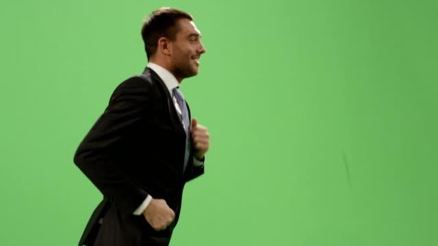 glad affärsman i kostym som körs på en mock-up grön skärm i bakgrunden. - kostym sida bildbanksvideor och videomaterial från bakom kulisserna