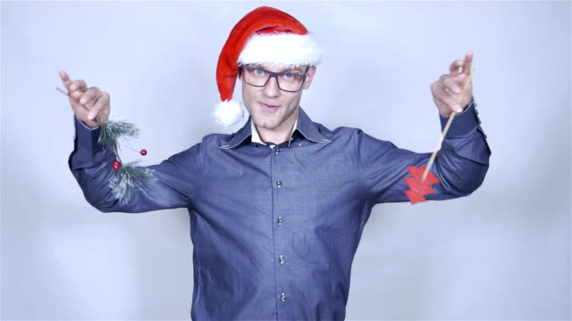 Happy businessman in christmas hat dancing over grey background. video