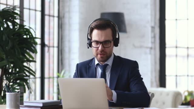 счастливый бизнесмен в официальном иске дает профессиональную финансовую консультацию онлайн. - дистанционный стоковые видео и кадры b-roll