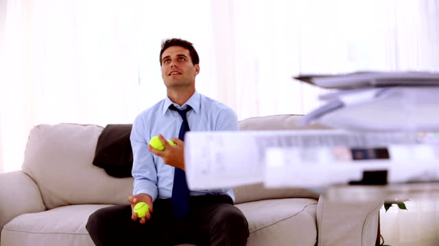 Happy businessman juggling with tennis ball video