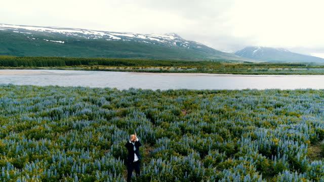stockvideo's en b-roll-footage met gelukkig zakenman op een weide vol bloemen - er even tussenuit
