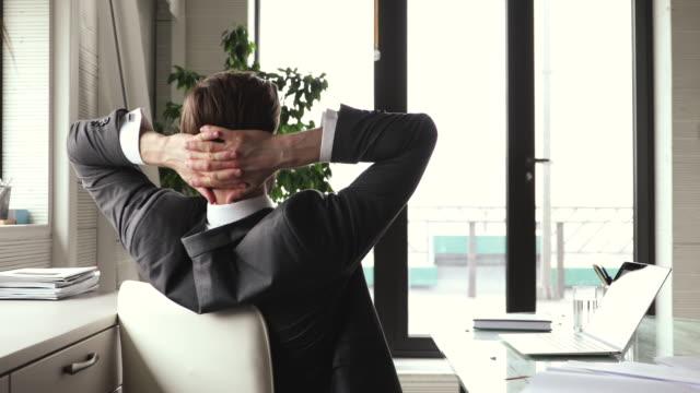 glad affärsman nöjd avslutat arbete med paus avkopplande på arbetsplatsen - människorygg bildbanksvideor och videomaterial från bakom kulisserna