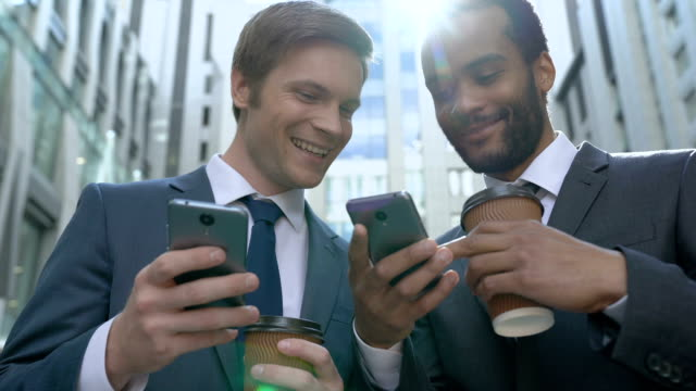 Happy businessmen using easy mobile app on smartphone, colleagues on lunch break