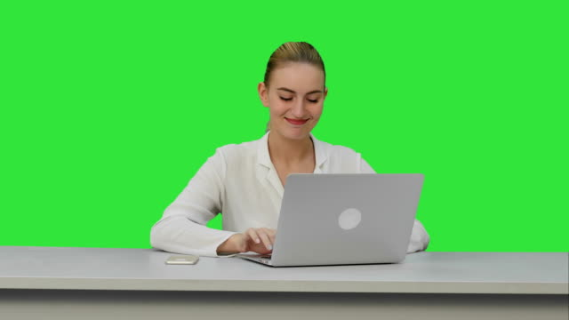 Happy businesswoman enjoy working on laptop computer, imagine the project and write down on a Green Screen, Chroma Key video