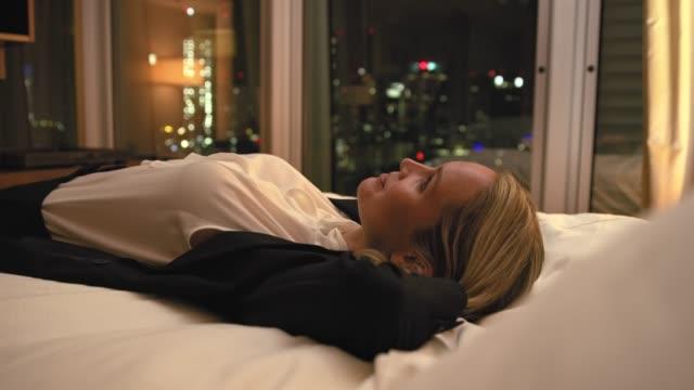 stockvideo's en b-roll-footage met happy zakenvrouw springen op bed in hotelkamer - zakenreis