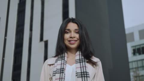 buona imprenditrice che guarda la telecamera per strada. donna d'affari sorridente all'aperto - capelli castani video stock e b–roll