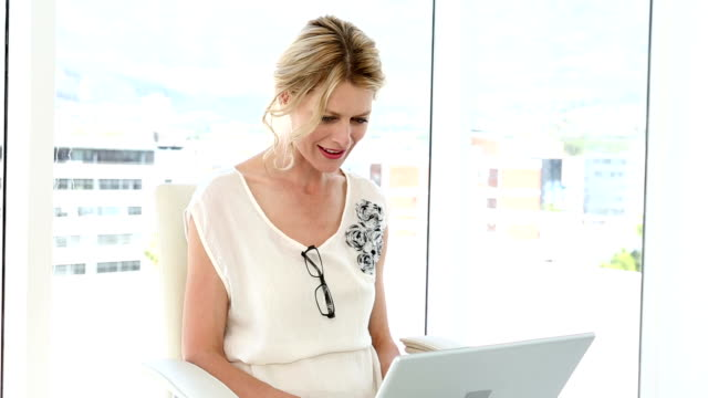 Happy businesswoman using video chat on laptop video