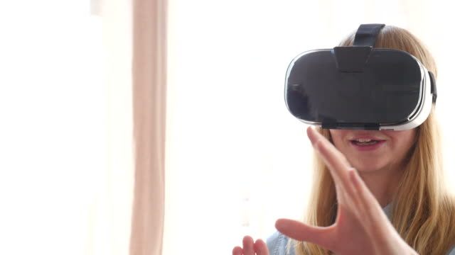 Happy Businesswoman Using VR Glasses In Office Handheld shot of happy businesswoman using VR glasses in brightly lit office. Female professional is gesturing and talking at workplace. She is standing with male colleague. less than 10 seconds stock videos & royalty-free footage