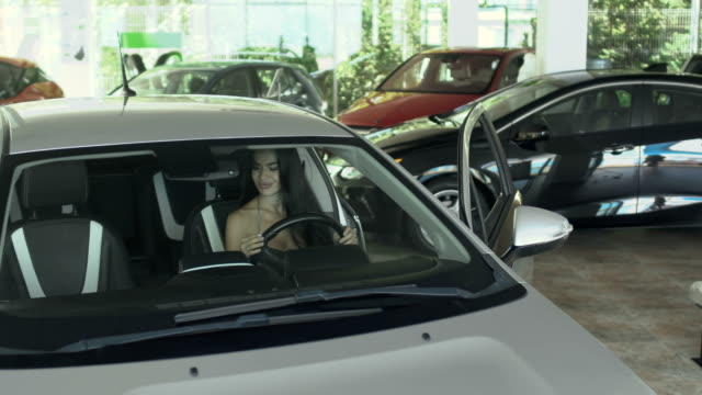 Happy businesswoman with keys just bought a new auto in car dealership Beautiful woman inspects automobile in the car dealership. Young girl touches the car from inside and observes it. The woman chooses auto in the car showroom. Portrait of stylish woman leans on the door of car, holds a keys and smiling. leaning stock videos & royalty-free footage