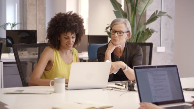 Happy businesswomen discussing over laptop at desk Happy businesswomen discussing over laptop at creative office. Female entrepreneurs are sitting while planning strategy at desk. They are in smart casuals. mid adult women stock videos & royalty-free footage