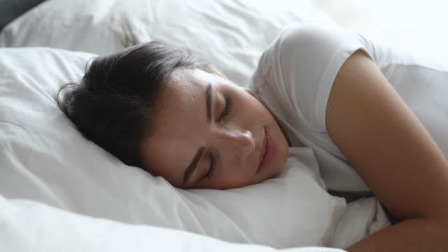 vídeos de stock e filmes b-roll de happy calm millennial woman sleeping in comfortable bed. - dormir