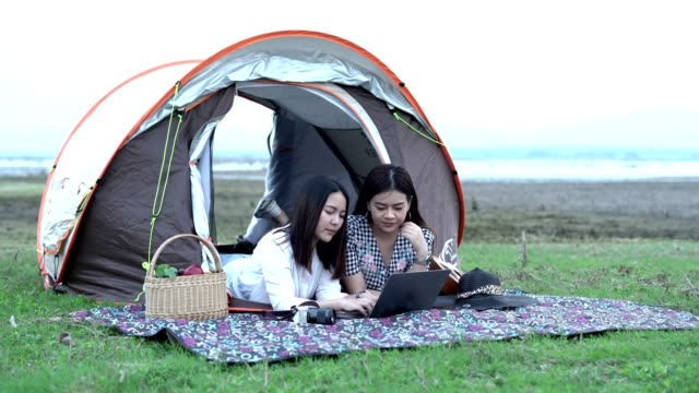 Happy campers lying in tent and using laptop