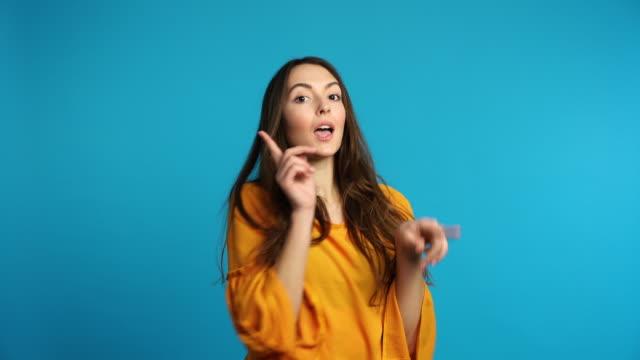 vidéos et rushes de femme insouciante heureuse dansant sur le fond bleu - d'ascendance européenne