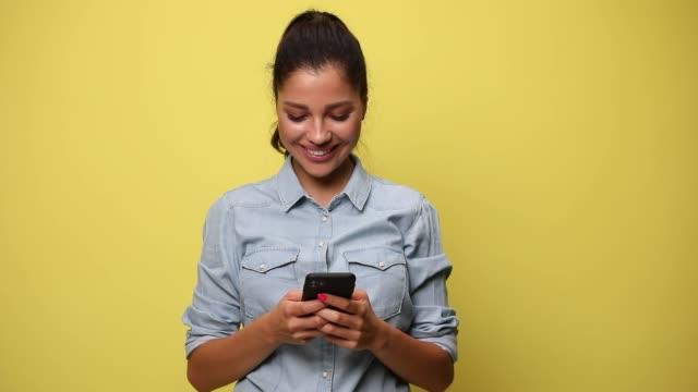 vídeos y material grabado en eventos de stock de chica casual feliz con camisa de mezclilla azul sonriendo, enviando mensajes de texto y leyendo correos electrónicos sobre fondo amarillo - amarillo color