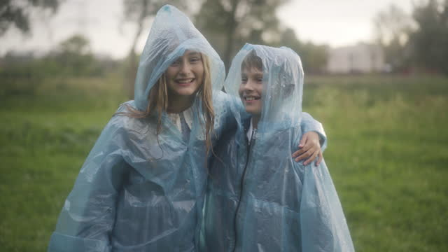 Happy Caucasian children in raincoats catching rain drops and smiling at camera. Positive boy and girl posing outdoors on rainy summer day. Happiness and childhood concept