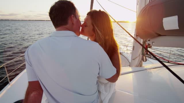 vídeos y material grabado en eventos de stock de feliz pareja caucásica beso al atardecer en el yate - planificación financiera