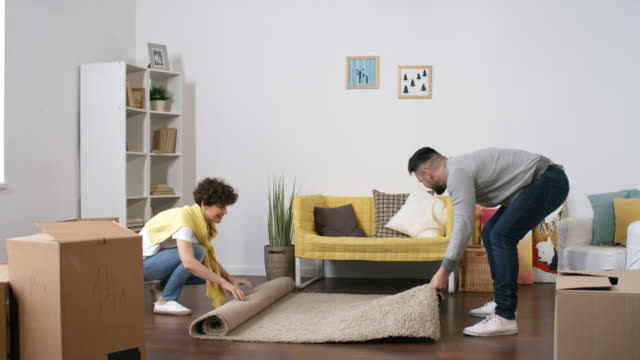 happy caucasian couple laying carpet in first home - tappeto video stock e b–roll