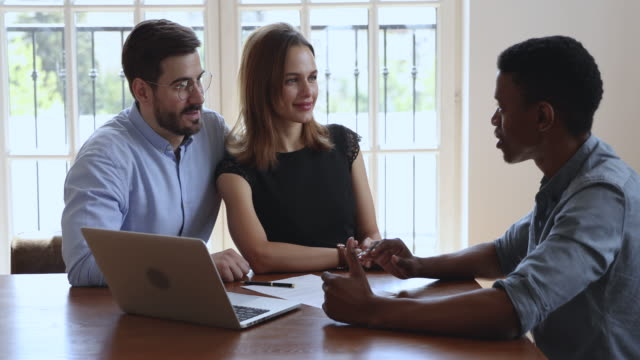 Happy caucasian couple listening african manager consulting about mortgage deal Happy young caucasian couple listening african lawyer bank manager consulting clients about mortgage loan investment insurance real estate deal, family customers talk to broker insurer at meeting salesman stock videos & royalty-free footage