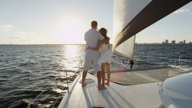 Happy Caucasian couple on luxury sail yacht vacation Young Caucasian happy male female couple tourism advertisement luxury sailing yacht financial planning laughing ambition RED EPIC yacht stock videos & royalty-free footage