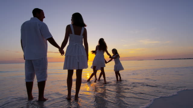 Happy Caucasian family together on a vacation beach young Caucasian family parents girls daughters casual travel lifestyle relaxation sunrise silhouette paradise beach ocean loving RED DRAGON wealth stock videos & royalty-free footage