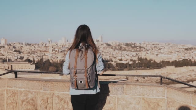 Happy Caucasian girl runs, arms wide open. View of Israel, Jerusalem old town. Excited female tourist. Slow motion video