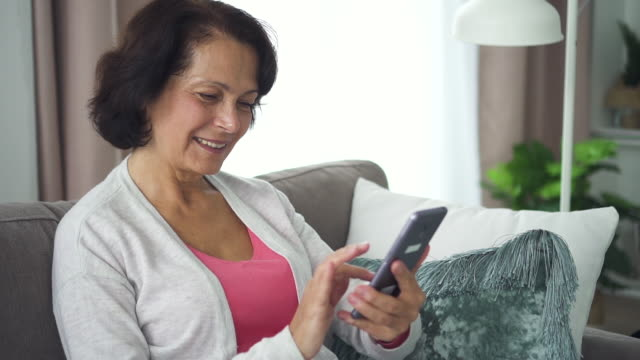 Happy caucasian mature woman using smartphone sitting at sofa in living room