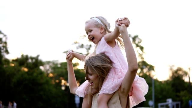 Glückliche kaukasische Mutter trägt schöne kleine Tochter auf ihren Schultern, tanzen und Spaß zusammen in öffentlichen, grünen Park. Tag frei, Mutterschaft – Video