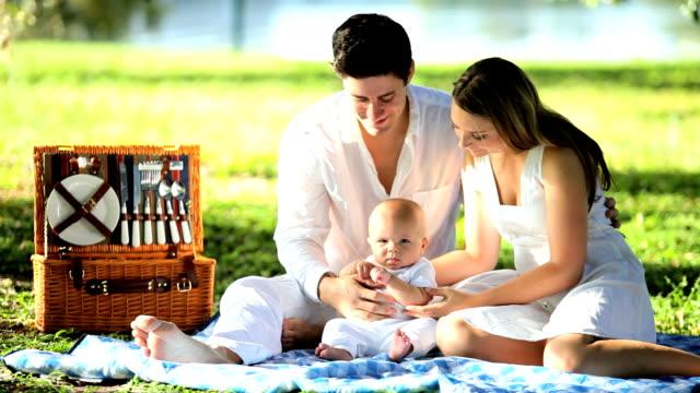 vídeos y material grabado en eventos de stock de caucásica felices padres park con hija bebé - nuevo bebé