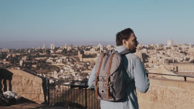 Happy Caucasian tourist male raises hands excited. Israel, Jerusalem. Man with arms wide open. Travel. Slow motion video