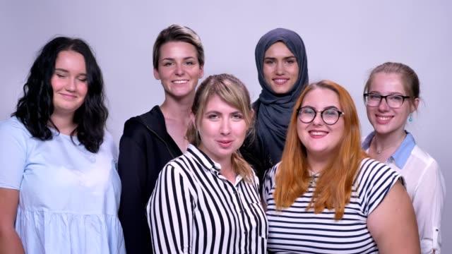glad kaukasiska till skillnad från kvinnor stå tillsammans kylning och leende inomhus - anständig klädsel bildbanksvideor och videomaterial från bakom kulisserna
